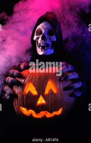 Skelett im Gewand einen geschnitzten Kürbis mit Monster Hände halten - Stockfoto