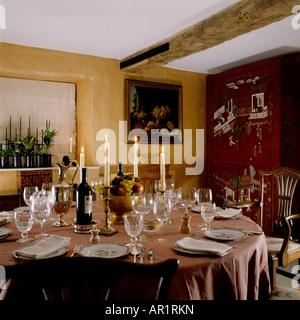 Esstisch mit brennenden Kerzen im Zimmer mit Deckenbalken - Stockfoto