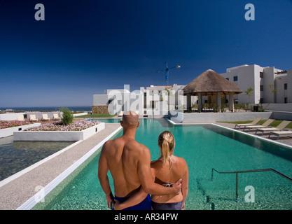 Spanien, paar stehend mit Arm in Arm Blick auf blauen Pool und apartments - Stockfoto