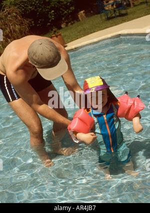 Kleiner Junge mit seinem Vater tragen einen UV Badeanzug in einem Schwimmbad im Urlaub in Korsika, Frankreich - Stockfoto