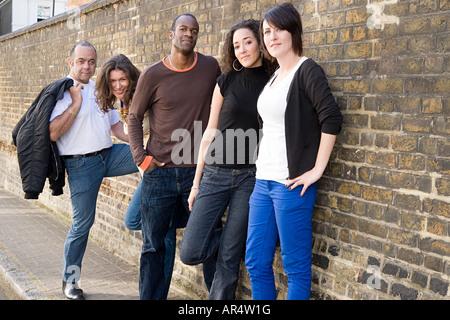 Fünf Menschen, die stehen auf einem Bürgersteig - Stockfoto