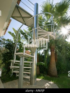 Edelstahl Wendeltreppe mit Palmen mit Sonnenschein, strahlend in - Stockfoto