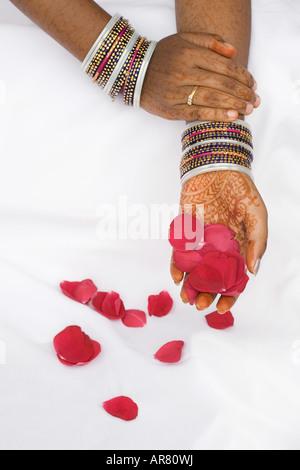 Inderin mit Henna Hände halten rote Rosenblüten - Stockfoto