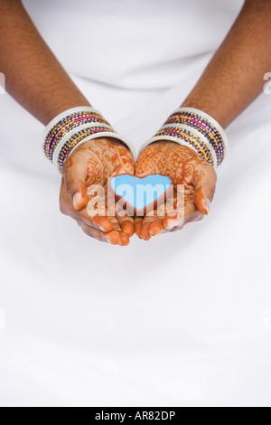 Inderin mit Henna Händen hält Herz geformten Schale. Indien - Stockfoto