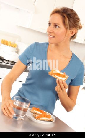 WOMAN EATING GERÄUCHERTER LACHS KNÄCKEBROT - Stockfoto