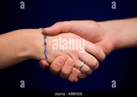 Männliche und weibliche informellen Handshake vor blauem Hintergrund - Stockfoto