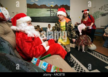 Freiwilliger Santa Claus und Frau Santa Hintergrund spielt mit einheimischen Kindern während Weihnachtsaktivitäten - Stockfoto