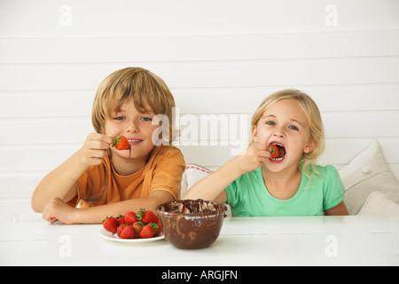 Kinder essen Erdbeeren und Schokolade