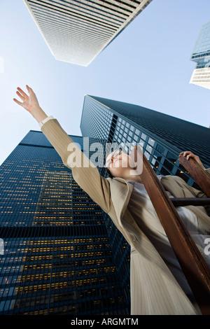 Geschäftsfrau steht auf der Leiter nach oben erreichen - Stockfoto