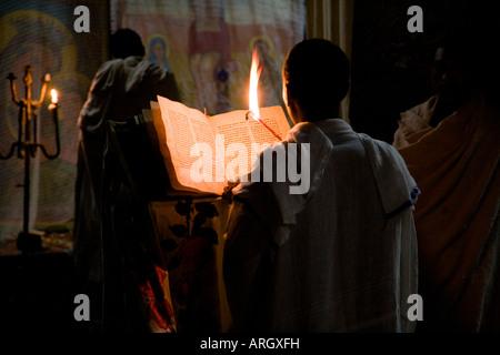 Rückansicht eines Mönchs Lesen der Bibel in einer Kirche Medhane Alem, Lalibela, Äthiopien - Stockfoto