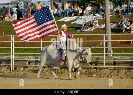 Weibliche Cowgirl reitet einen Brama Stier die Flagge in der Zeremonie vor einem rodeo - Stockfoto