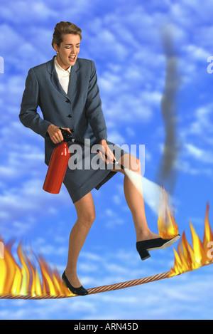 Geschäftsfrau, die erlöschen die Flammen zu Fuß - Stockfoto