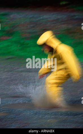 Junge in gelben Regenmantel Tritte Pfütze, Bewegungsunschärfe, British Columbia, Kanada. - Stockfoto