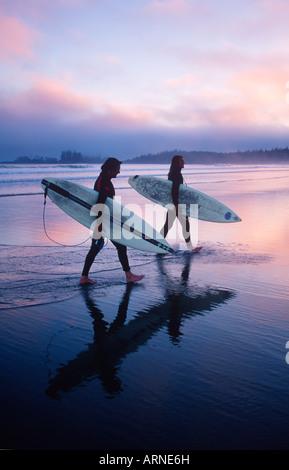 zwei junge männliche Surfer zu Fuß mit ihren Brettern auf der Strand, Pacific Rim, Kish, Vancouver Island, British - Stockfoto
