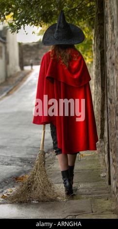 Rückansicht einer jungen Frau trägt einen roten Umhang und ein Hexenhut ziehen einen Besenstiel zu Fuß in einer - Stockfoto