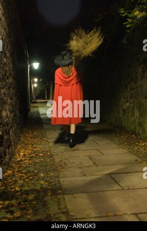 Hinten Wiew einer jungen Frau trägt einen roten Umhang und Hexe Hut nachts in einer einsamen Gasse - Stockfoto