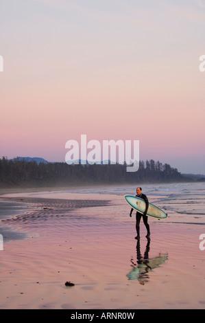 Surfer geht Küstenlinie, Pacific Rim National Park, Long Beach, Vancouver Island, British Columbia, Kanada. - Stockfoto
