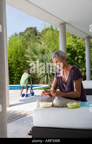 Frau Peeling Obst junge im Hintergrund - Stockfoto