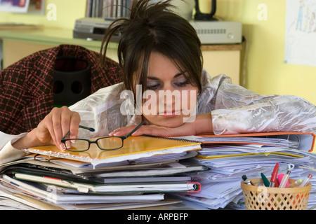 junge Frau am Schreibtisch, umgeben durch Berge von Papierkram betonte - Stockfoto