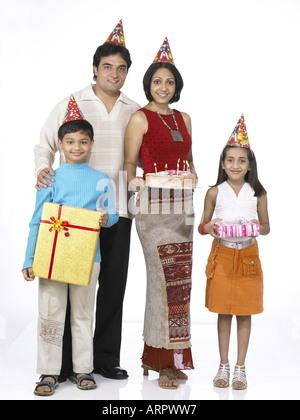 Südasiatische indische Familie einkaufen Kuchen Weihnachtsgeschenke mit Vater Mutter Sohn und Tochter tragen Dunce - Stockfoto