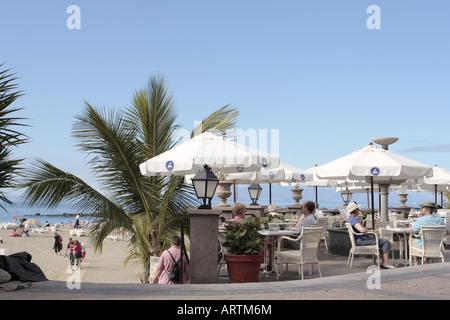 Kaffeetrinken auf der Promenade oberhalb des Strandes von Playa del Duque an der Costa Adeje Teneriffa Kanaren Spanien - Stockfoto