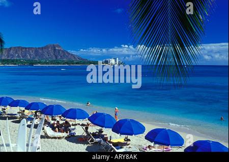 Urlauber genießen eine Aussicht auf Diamond Head Krater, wie sie am einladenden Sandstrand von Waikiki Beach.This - Stockfoto