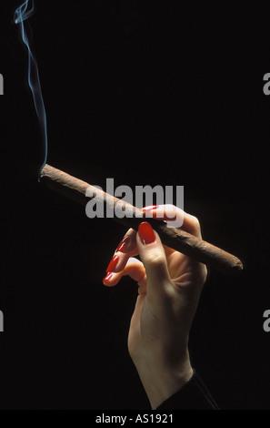 Woman's Hand leuchtet eine Zigarre Trailing Rauch, auf schwarzem Hintergrund Silhouette - Stockfoto