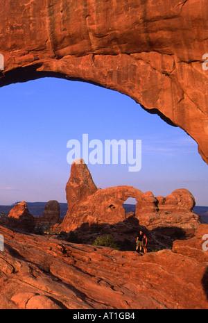 Junges Paar im Norden Fensterbogen mit Turret Arch stehen im Hintergrund, Arches-Nationalpark, Utah, USA - Stockfoto