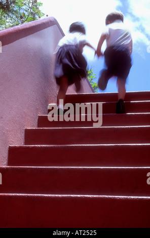 Zwei Kinder Hand in Hand laufen im Obergeschoss an der junior school - Stockfoto