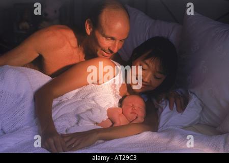 Kaukasische Vater und asiatische Mutter im Bett mit Neugeborenen - Stockfoto