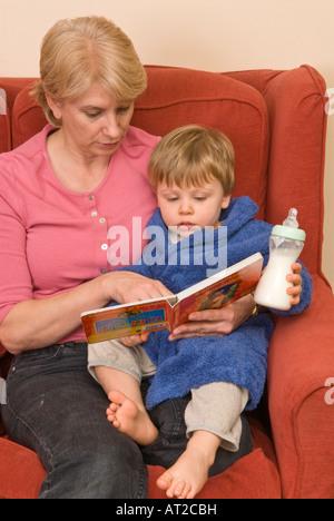 Großmutter Kindermädchen ältere Mutter Tagesmutter Lesung Sohn Enkel, die krank oder müde ist - Stockfoto