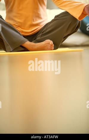 Sitzt eine Frau überquerte Beinen auf einer Yogamatte, Nahaufnahme - Stockfoto