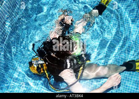 Ein Teilnehmer sitzt unter Wasser während des Unterrichts in einer Lektion indoor Tauchen Tauchen im Hallenbad - Stockfoto