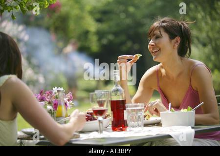 Zwei Frauen sitzen draußen an einem Tisch essen - Stockfoto