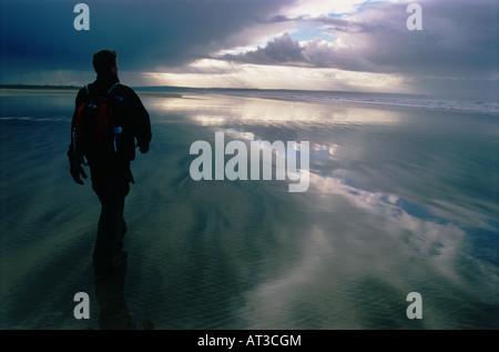 Ein Mann zu Fuß am Strand - Stockfoto