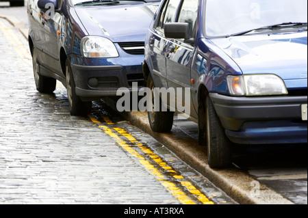 zwei Autos geparkt auf hellen gelben Doppellinien keine Parkplatz-Straßenmarkierungen - Stockfoto