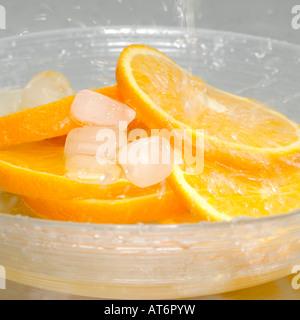Scheiben von Orange mit Eiswürfeln in Schüssel