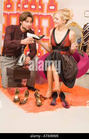 Mann verzweifelt an Freundin im Schuhgeschäft - Stockfoto