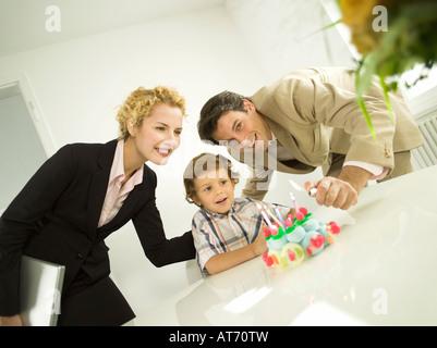 Junge Familie, Vater Anzünden von Kerzen auf der Geburtstagstorte - Stockfoto