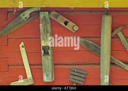 alte historische Werkzeuge von Zimmermann und Landwirt hängen rote Holzwand - Stockfoto