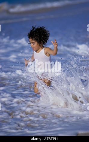 Ein junges Mädchen läuft durch die Wellen an der Küste von einem Strand auf der Insel Oahu. - Stockfoto