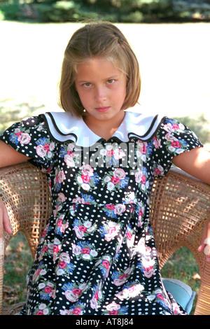Mädchen verkleidet 9 Jahre alt und sitzt in einem Korbstuhl mit Haltung. Western Springs, Illinois USA - Stockfoto