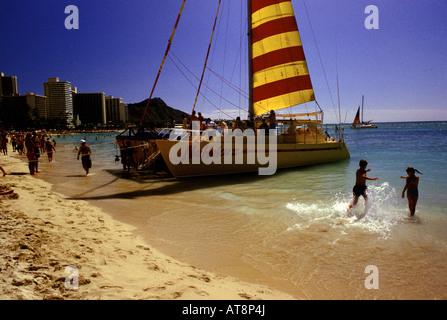 Touristen auf dem Deck eines großen Katamarans mit roten und gelben gestreiften Segel am Strand von Waikiki zu sammeln. - Stockfoto