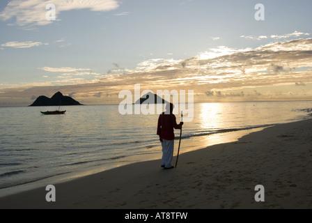 Mann mit Spazierstock Spaziergänge entlang der Küstenlinie von Lanikai Strand bei Sonnenaufgang mit den Mokulua - Stockfoto