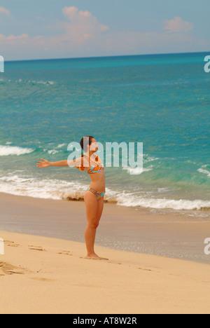 Junge Frau am Strand mit ausgestreckten Armen - Stockfoto