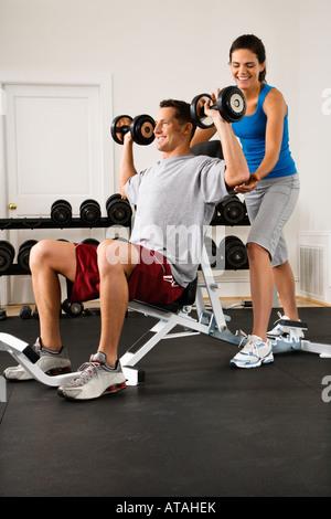 Frau Mann Heben von Gewichten im Fitnessstudio zu unterstützen - Stockfoto