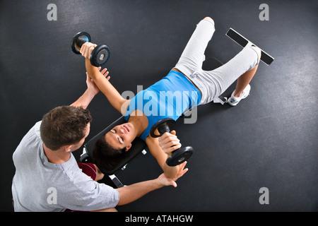Mann unterstützt Frau Heben von Gewichten im Fitnessstudio - Stockfoto