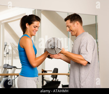 Mann und Frau im Fitnessstudio Gewichte heben - Stockfoto