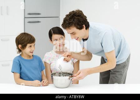 Vater und zwei Kinder backen zusammen, Mann mit elektrischen mixer - Stockfoto