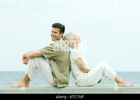 Ältere Frau und erwachsener Sohn sitzen Rücken an Rücken am Meer, Seitenansicht - Stockfoto